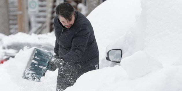 Danny Luis shovels snow around his car after a late winter storm in Montreal on March 15, 2017.