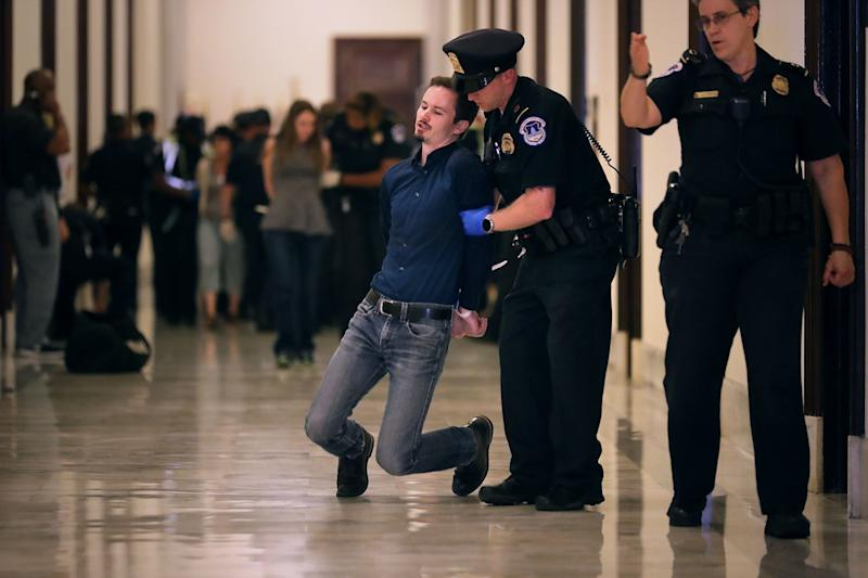 Demonstrators are lead away in handcuffs.