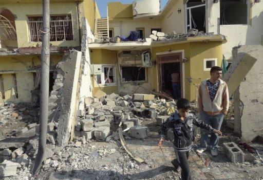 A man and boy look at a building damaged by one of three car bomb attacks in Kirkuk, Iraq, on November 27, 2012