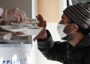 A volunteer serves food and drinks to a homeless man in Milan, Italy, Saturday, Nov. 7, 2020. As the Italian government placed four regions, including hard-hit Lombardy, into effective lockdown for two weeks because infections and hospital saturation levels were rising fast, canteens and shelters for homeless people had to be shut down, leaving them with nowhere to get a meal. (AP Photo/Antonio Calanni)