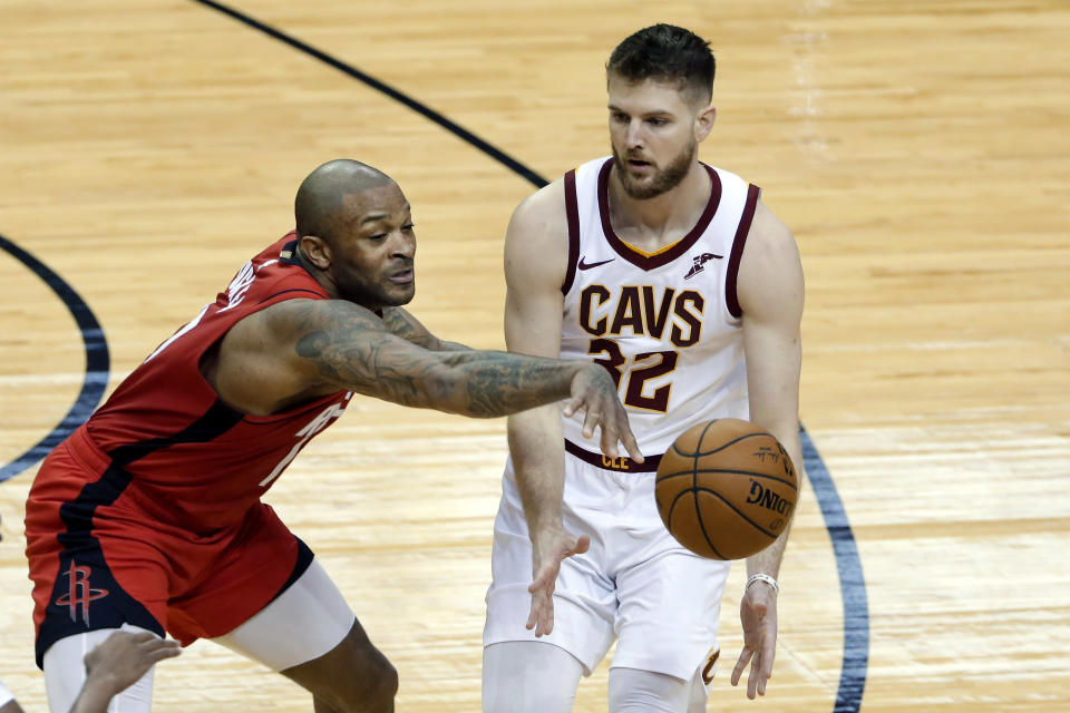 File-This March 1, 2021, file photo shows Cleveland Cavaliers forward Dean Wade (32) passing the ball as Houston Rockets forward P.J. Tucker (17) reaches in to knock it away during the first half of an NBA basketball game in Houston. Tucker says a move to the championship-contending Milwaukee Bucks offers the 35-year-old veteran a breath of fresh air and a chance to turn around a personally frustrating season. Tucker practiced with his new team Friday, March 19, 2021, after the Bucks officially announced they had acquired the 6-foot-5 forward along with guard Rodions Kurucs from the Houston Rockets. (AP Photo/Michael Wyke, File)