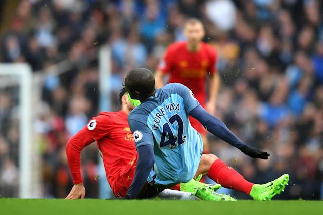 <p>Studs up: Yaya Toure launches into a dangerous tackle on Emre Can </p>