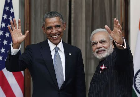 U.S. President Obama and India's PM Modi wave towards the media during a photo opportunity ahead of their meeting at Hyderabad House in New Delhi