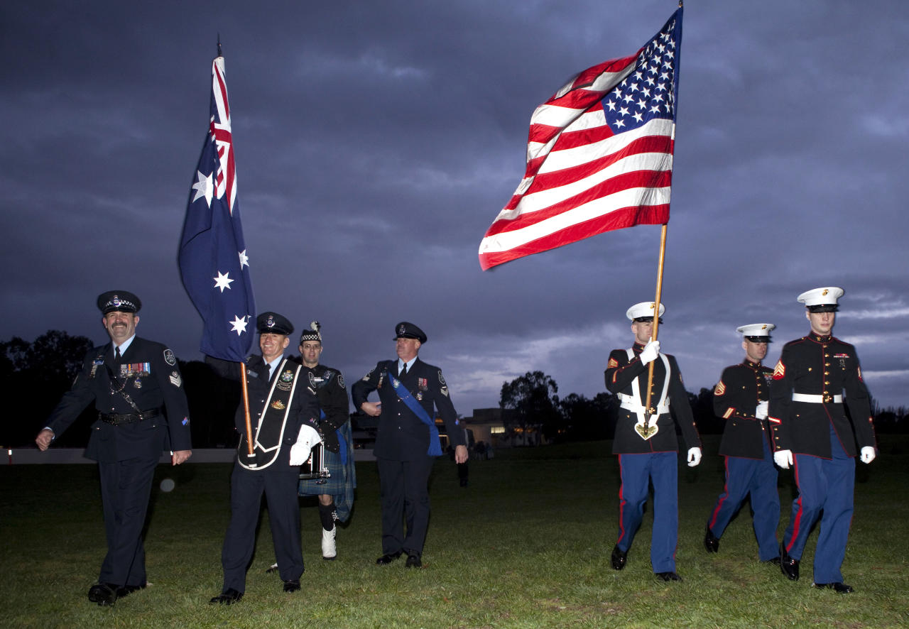The Australian and American flags are withdrawn after a remembrance service marking the 10th anniversary of the Sept. 11 attacks in the US, in Canberra, Australia, Sunday, Sept. 11, 2011.  (AP Photo/Andrew Taylor)