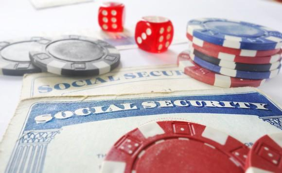 Dice and casino chips lying on Social Security cards.