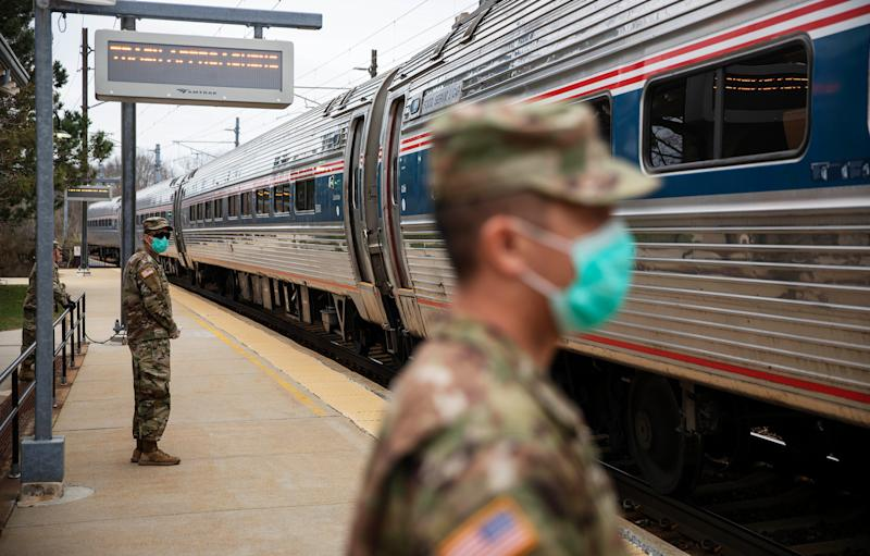 Members of the Rhode Island National Guard check for passengers getting off a train from New York as it arrives March 28 in Westerly, R.I.