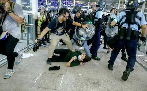 Riot police stormed part of the airport as protesters crippled terminals - Credit: THOMAS PETER/ REUTERS