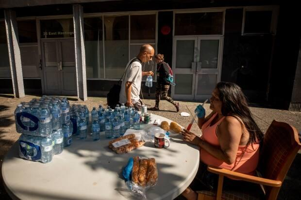 A woman who goes by the name ChillyBean hands out bottled water to residents in the Downtown Eastside neighbourhood in Vancouver on Monday. (Ben Nelms/CBC - image credit)
