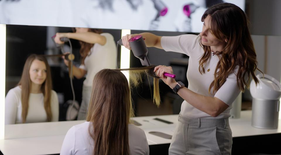Woman blowdrying hair with a Dyson hairdryer