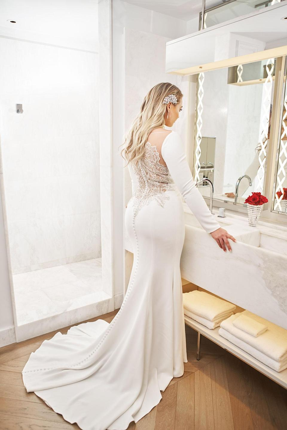 <p>Lawrence wears a long sleeve white gown with intricate lace details on the back by Justin Alexander. (Photo: courtesy of Justin Alexander) </p>