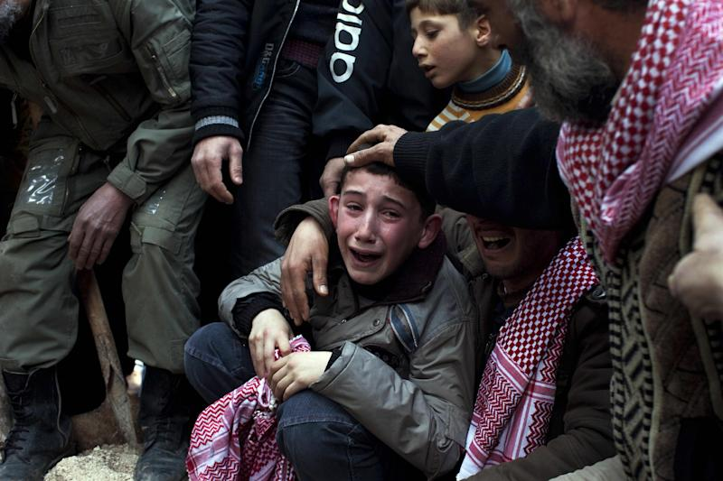 FILE - In this March 8, 2012 file photo, A boy named Ahmed mourns his father, Abdulaziz Abu Ahmed Khrer, who was killed by a Syrian army sniper, during his funeral in Idlib, northern Syria. More than 100,000 people have been killed since the start of Syria's conflict over two years ago, an activist group said Wednesday. (AP Photo/Rodrigo Abd, File)