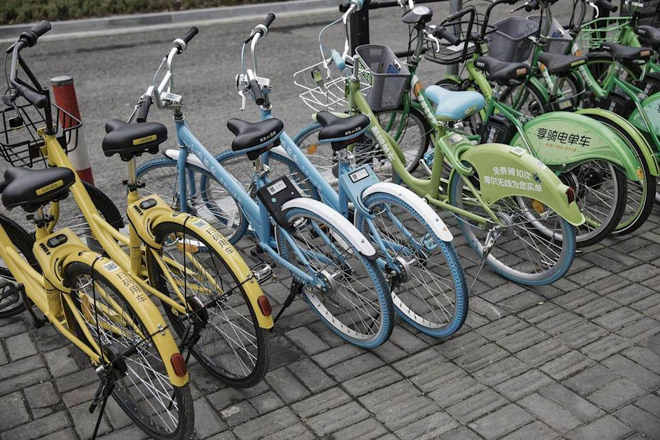 Ofo Inc., left and second left, Xiaoming Danche, third and fourth left, and other bicycles stand parked on a sidewalk in Shanghai, China, on Thursday, May 25, 2017. In China, Qilai Shen/Bloomberg