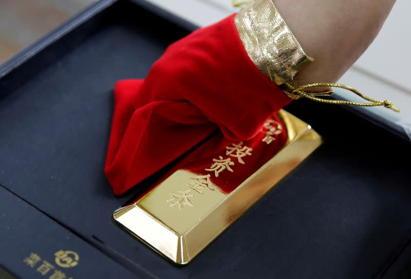 FILE PHOTO: A sales assistant displays a 1000 gram gold bar as an investment for a customer at Caibai Jewelry store in Beijing