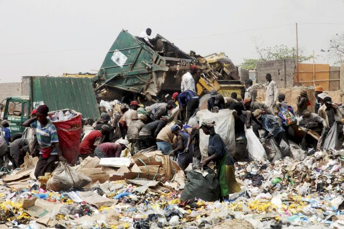 Scavengers pick up trash for recycling at the Olusosun dump site in Nigeria's commercial capital Lagos in this March 23, 2012 file photo. One thing Nigeria's megacity of Lagos, one of the world's largest, generates in abundance is trash. Now it plans to turn that rubbish into electricity which the city desperately lacks. Ola Oresanya, managing director of the Lagos Waste Management Authority (LAWMA) aims to complete the project in around five years, by which time it will have a 25 megawatt (mw) capacity, he said. That is only 1 percent of the 2,000 - 3,000 mw that he estimates Lagosians demand, but it is a start. To match story NIGERIA-RUBBISH/ELECTRICITY/ REUTERS/Akintunde Akinleye/Files (NIGERIA - Tags: ENERGY SOCIETY)