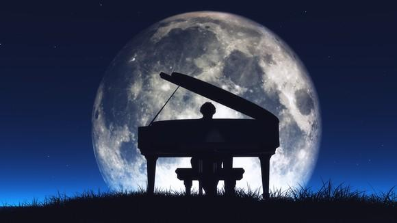 Piano and pianist silhouetted against the moon