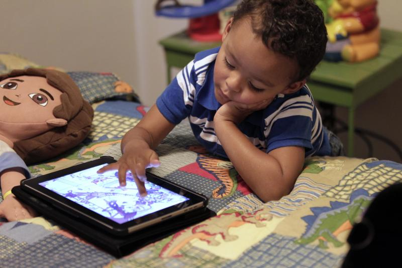 FILE - In this Friday, Oct. 21, 2011 file photo, Frankie Thevenot, 3, plays with an iPad in his bedroom at his home in Metairie, La. As of Wednesday, Aug. 7, 2013, the Campaign for a Commercial-Free Childhood, a Boston-based group, is urging federal investigators to examine the marketing practices of Fisher-Price's and Open Solution's mobile apps. It's the campaign's first complaint against the mobile app industry as part of its broader push to hold accountable businesses that market technology to very young children and their parents. (AP Photo/Gerald Herbert, File)