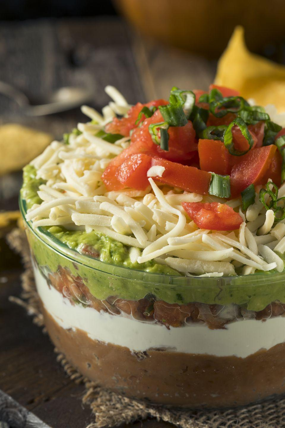"""<p>At only 100 calories a serving, here's a dip you can feel good about diving into.</p><p><a href=""""https://www.goodhousekeeping.com/food-recipes/a11044/seven-layer-dip-recipe-ghk0911/"""" rel=""""nofollow noopener"""" target=""""_blank"""" data-ylk=""""slk:Get the recipe for Healthy Seven Layer Dip »"""" class=""""link rapid-noclick-resp""""><em>Get the recipe for Healthy Seven Layer Dip »</em></a></p>"""