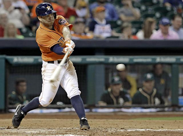 Houston Astros' Jose Altuve hits the ball to Oakland Athletics third baseman Josh Donaldson in the fourth inning of a baseball game on Friday, April 25, 2014, in Houston. Donaldson overthrew the ball to first, sending Altuve to second base and allowing two runners to score. (AP Photo/Pat Sullivan)