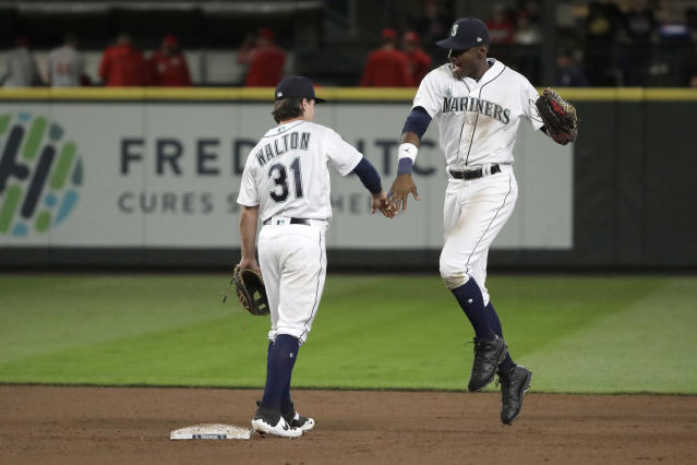 Seattle Mariners' Kyle Lewis, right, celebrates with shortstop Donnie Walton after the team's baseball game against the Cincinnati Reds, Tuesday, Sept. 10, 2019, in Seattle. The Mariners won 4-3 as both players made their major league debuts. (AP Photo/Ted S. Warren)