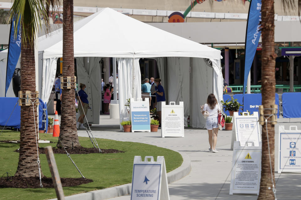 A tent outside the Magic Kingdom screens arriving guests during the first days of reopening at Walt Disney World, Saturday, July 11, 2020, in Lake Buena Vista, Fla. (AP Photo/John Raoux)