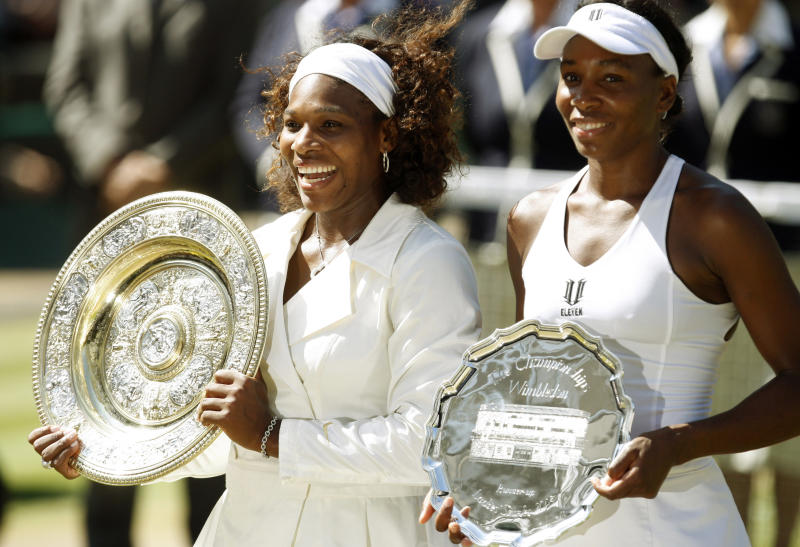 ADVANCE FOR WEEKEND EDTIONS, JUNE 18-19 - FILE - In this July 4, 2009 file photo, Serena Williams left, holds the championship trophy, after defeating her sister Venus, who holds the runners-up trophy, in the women's singles final on Centre Court at Wimbledon.  (AP Photo/Alastair Grant, File)
