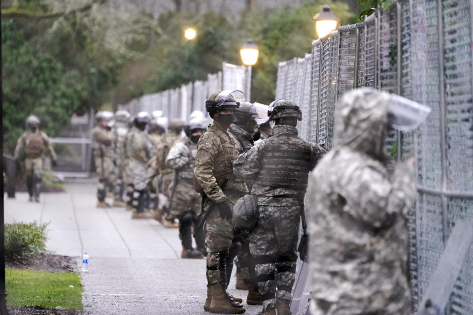 Members of the Washington National Guard stand at a fence surrounding the Capitol in anticipation of protests Monday, Jan. 11, 2021, in Olympia, Wash. State capitols across the country are under heightened security after the siege of the U.S. Capitol last week. (AP Photo/Ted S. Warren)