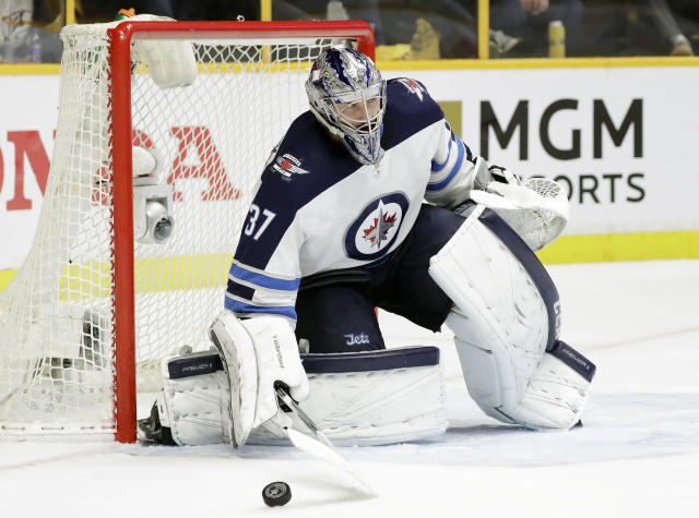 Winnipeg Jets goalie Connor Hellebuyck blocks a shot from the Nashville Predators during the second period in Game 1 of an NHL hockey second-round playoff series Friday, April 27, 2018, in Nashville, Tenn. (AP Photo/Mark Humphrey)