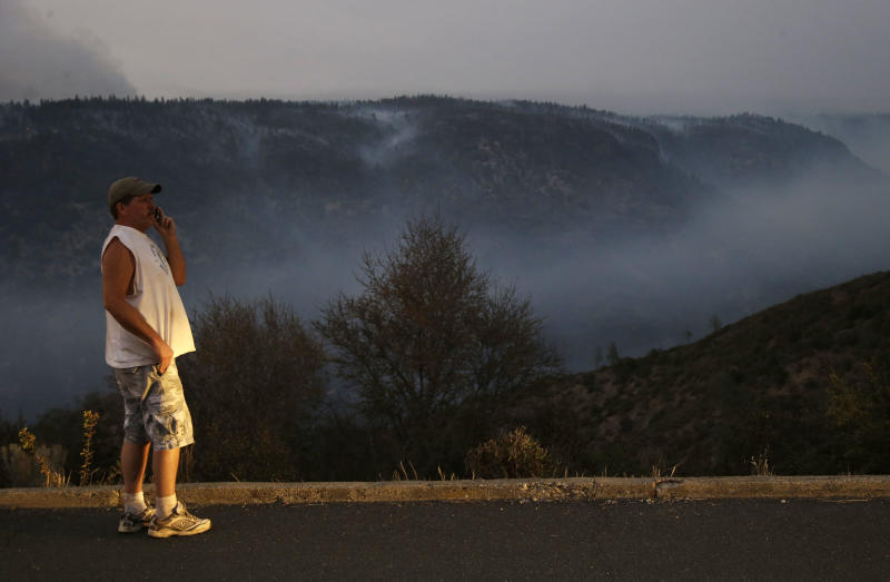 Wayne Athey watches smoke from the Ponderosa Fire from a lookout point near Mineral, Calif., Thursday, Aug. 23, 2012. Fire crews saved Athey's cabin along Ponderosa Way in the Battle Creek Canyon region. The Ponderosa Fire was 57 percent contained, with full containment expected early next week. The blaze threatened 900 other homes Thursday as it burned a new front to the south. More than 2,500 firefighters are battling the wildfire, which grew to 44 square miles in the hills about 25 miles southeast of Redding. (AP Photo/Marcio Jose Sanchez)