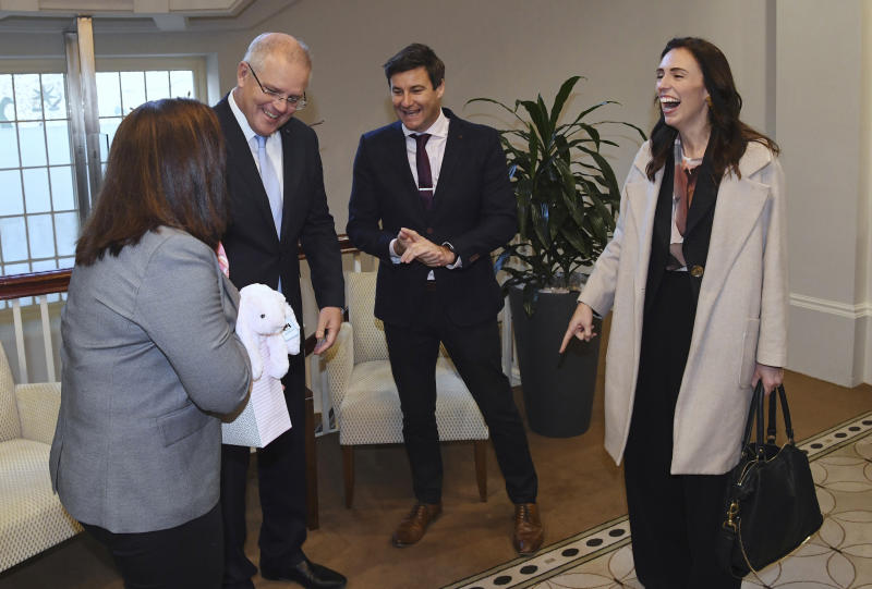 New Zealand's Prime Minister Jacinda Ardern, right, accompanied by her husband Clarke Gayford, second right, points at a gift of a soft toy from Australian Prime Minister Scott Morrison, second left, and his wife Jenny in Melbourne, Australia, Friday, July 19, 2019. (Julian Smith/Pool Photo via AP)