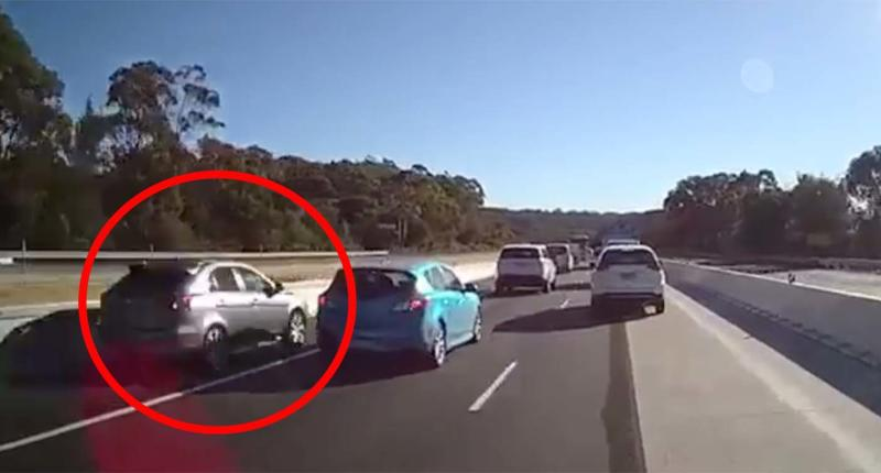 A silver hatchback is seen using an emergency stopping lane to overtake cars on a highway near Gosford on the Central Coast.