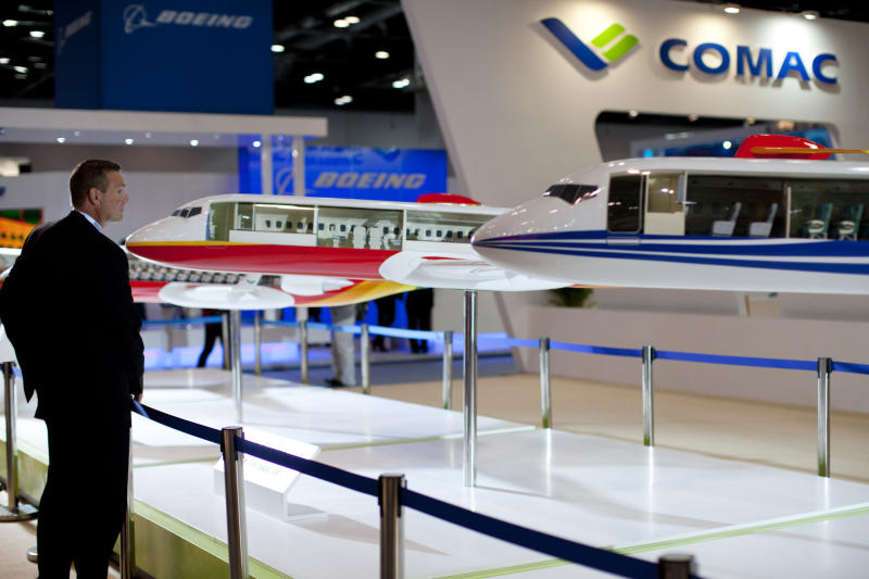 An attendee checks a model of China's first homegrown commercial jet airliner ARJ 21, painted red in center, at an aviation expo in Beijing, Wednesday, Sept. 25, 2013. The delivery date of the 90-seat ARJ21 has been pushed back again, the manufacturer said Wednesday, the latest setback for China's ambitions to challenge market leaders Boeing and Airbus. (AP Photo/Alexander F. Yuan)