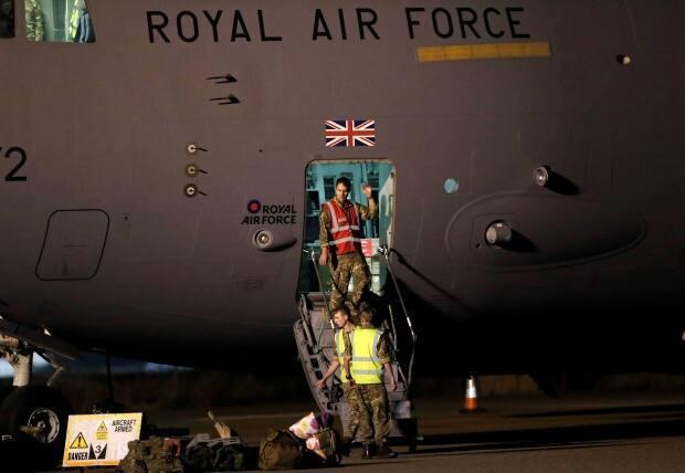 Members of the British armed forces who were deployed in Afghanistan disembark a C-17 aircraft after landing at Brize Norton, near Oxford, U.K., on Sunday.  (Peter Nicholls/Reuters - image credit)