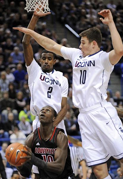 Louisville's Gorgui Dieng, bottom, is guarded by Connecticut's DeAndre Daniels (2) and Tyler Olander during the first half of an NCAA college basketball game in Hartford, Conn., Monday, Jan. 14, 2013. (AP Photo/Fred Beckham)