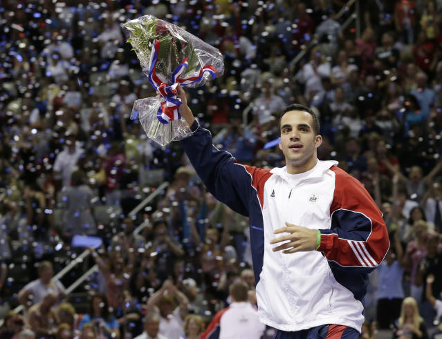 Danell Leyva acknowledges applause from the crowd as he is introduced as a member of the U.S. men's Olympic gymnastics team after the final round of the women's Olympic gymnastics trials, Sunday, July 1, 2012, in San Jose, Calif. (AP Photo/Gregory Bull)