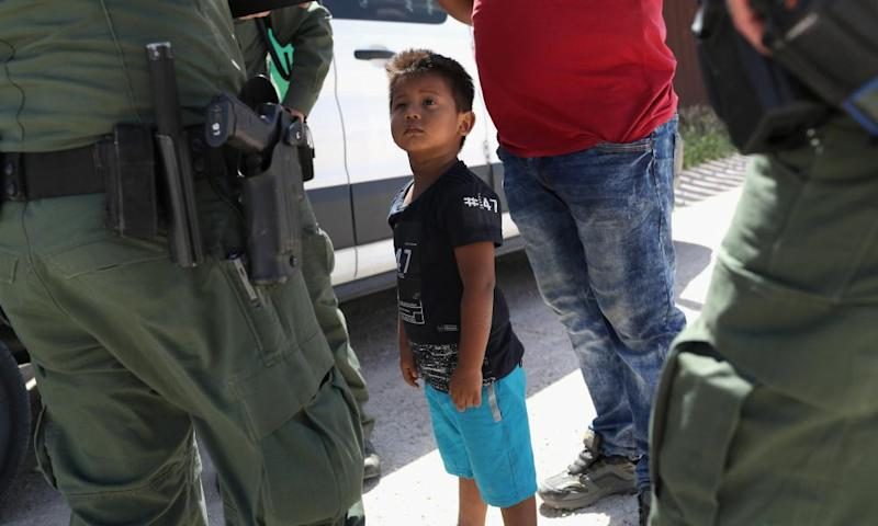 A boy and father from Honduras are taken into custody by US border patrol agents near Mission, Texas, on 12 June, and then sent to a processing center for possible separation.