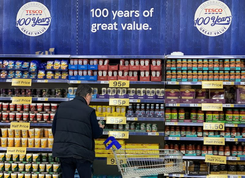 FILE PHOTO: A man looks at products on a shelf inside a Tesco Extra superstore near Manchester