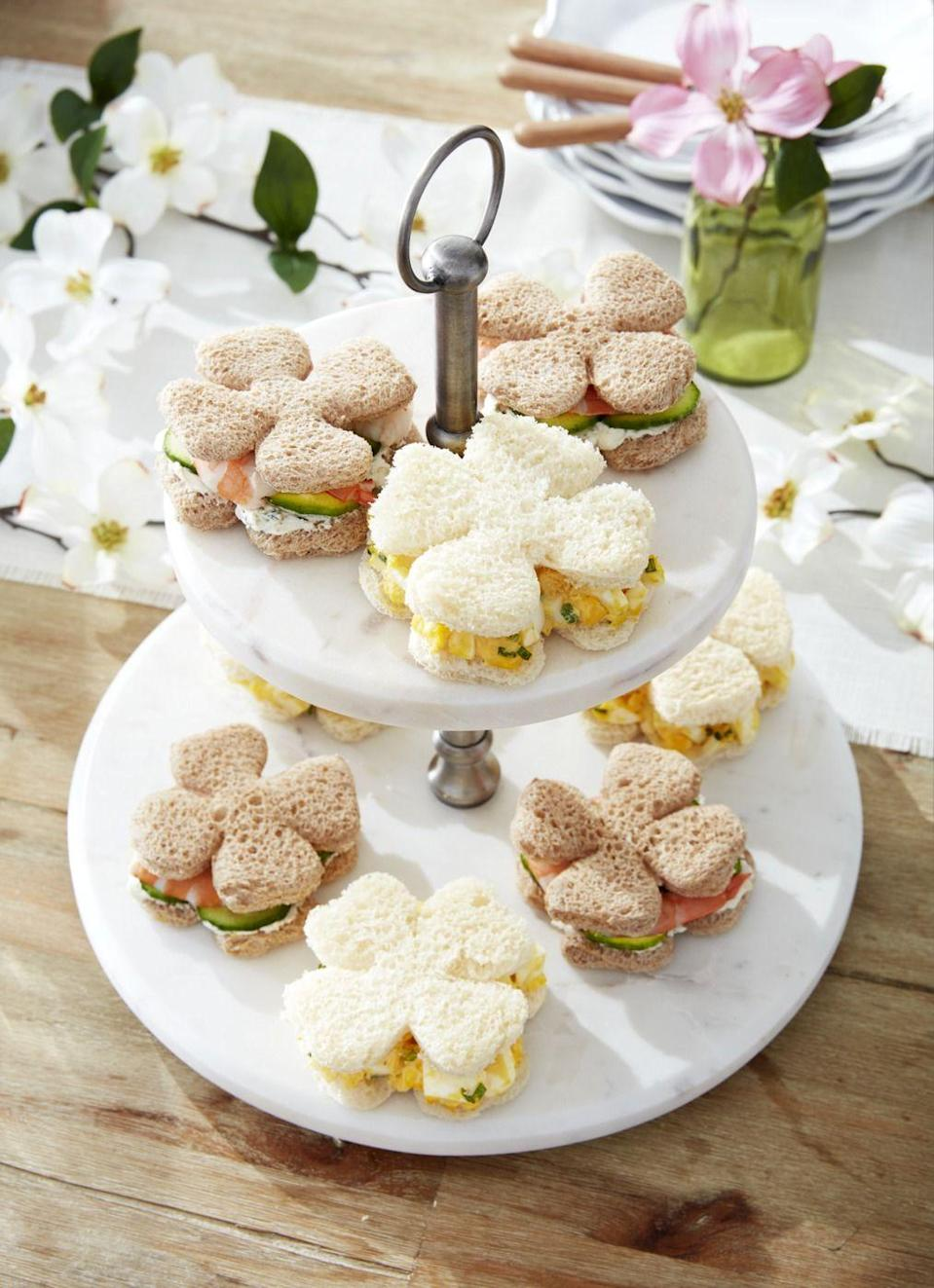 """<p>Use a clover cookie cutter and cut off the stem to make these sweet shapes, filled with your favorite ingredients, such as egg salad or salmon and cucumber.</p><p><strong><a href=""""https://www.countryliving.com/food-drinks/recipes/a33763/egg-salad-capers-red-onion-lemon-dill-recipe-wdy0513/"""" rel=""""nofollow noopener"""" target=""""_blank"""" data-ylk=""""slk:Get the recipe for egg salad"""" class=""""link rapid-noclick-resp"""">Get the recipe for egg salad</a>.</strong></p><p><a class=""""link rapid-noclick-resp"""" href=""""https://www.amazon.com/Cupcake-Plastic-Serving-Dessert-Birthday/dp/B07TLKBZJ6/?tag=syn-yahoo-20&ascsubtag=%5Bartid%7C10050.g.1642%5Bsrc%7Cyahoo-us"""" rel=""""nofollow noopener"""" target=""""_blank"""" data-ylk=""""slk:SHOP TIERED STAND"""">SHOP TIERED STAND</a></p>"""