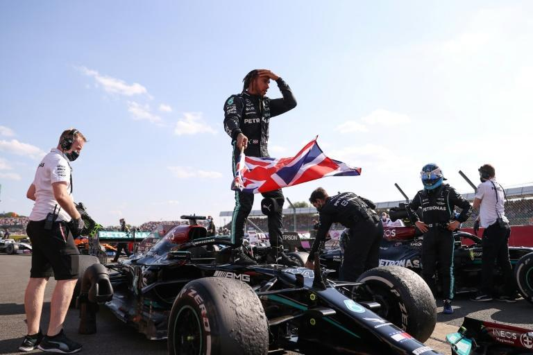 Flying the flag: Hamilton hit 99 with an eighth home victory (AFP/LARS BARON)