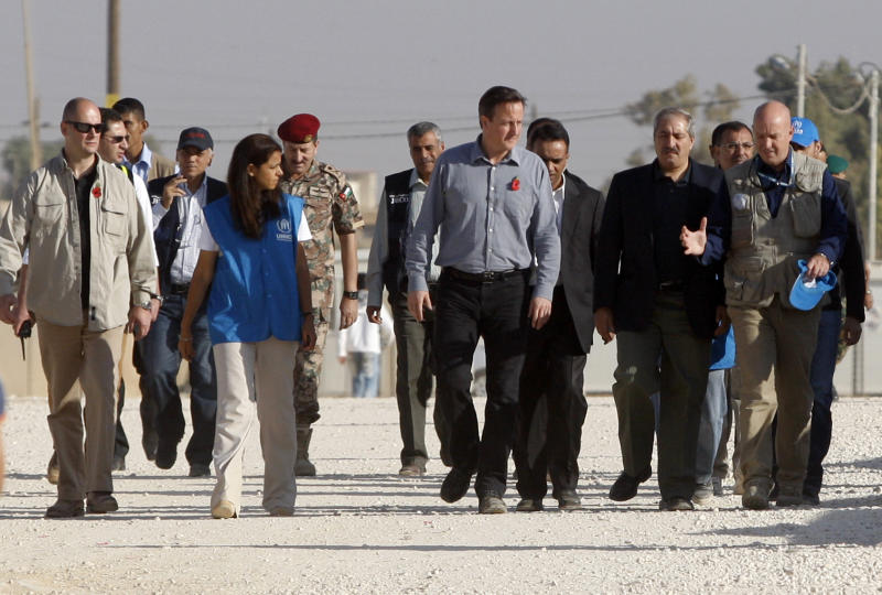 "Britain's Prime Minister David Cameron, center, walks with Jordanian Foreign Minister Nasser Judeh, second left, and United Nations High Commissioner for Refugees (UNHCR) representative to Jordan Andrew Harper, right, during his visit to Zaatari refugee camp in Mafraq, Jordan, Wednesday, Nov. 7, 2012. British Prime Minister David Cameron, visiting a camp for Syrian refugees in Jordan, said the U.S., Britain and other allies should do more to ""shape the opposition"" into a coherent force and open channels of communication directly with rebel military commanders. Previously, Britain and the U.S. have acknowledged contacts only with exile groups and political opposition figures inside Syria. (AP Photo)"