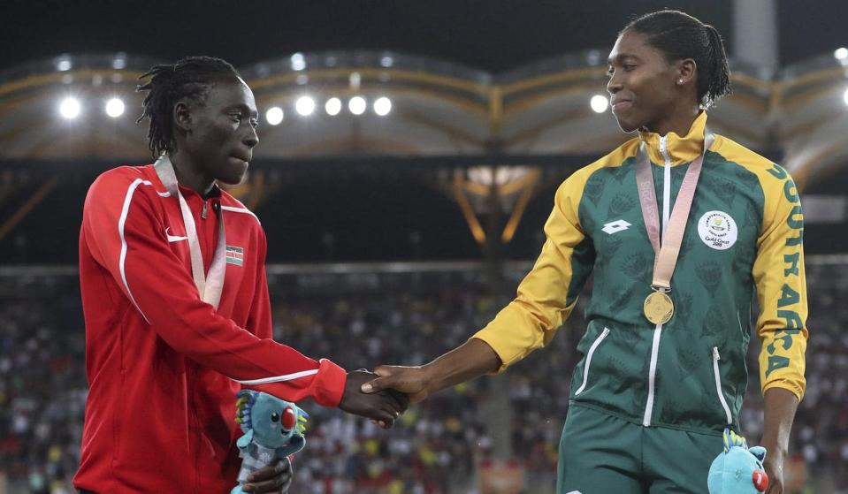 """<span class=""""caption"""">Women's 800-metre silver medal winner Margaret Nyairera Wambui, left, shakes hands with gold medal winner Caster Semenya on the podium at the 2018 Commonwealth Games in Australia. Both runners have refused to take hormone-reducing drugs so they could compete at the Tokyo Olympics.</span> <span class=""""attribution""""><span class=""""source"""">(AP Photo/Mark Schiefelbein)</span></span>"""