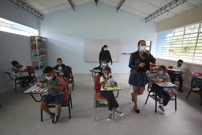 Wearing masks to curb the spread of the new coronavirus, students attend class in the one open school in Campohermoso, Colombia, Thursday, March 18, 2021. Campohermoso is one of two municipalities in Colombia that has not had a single case of COVID-19 since the pandemic started one year ago, with the student body at the school rotating half the students into their classrooms while the other attends via the internet. (AP Photo/Fernando Vergara)