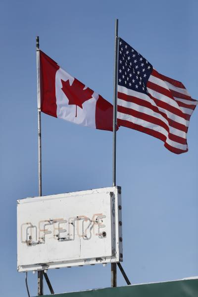FILE- In this Feb. 9, 2017, file photo, an American flag and a Canadian flag fly above Maple Leaf Motel's office in Emerson, Manitoba. America's neighbor to the north is increasingly being seen as a haven for asylum seekers turned away by the U.S. And some are willing to risk a walk across the border in dangerous cold to get there. (John Woods/The Canadian Press via AP, File)
