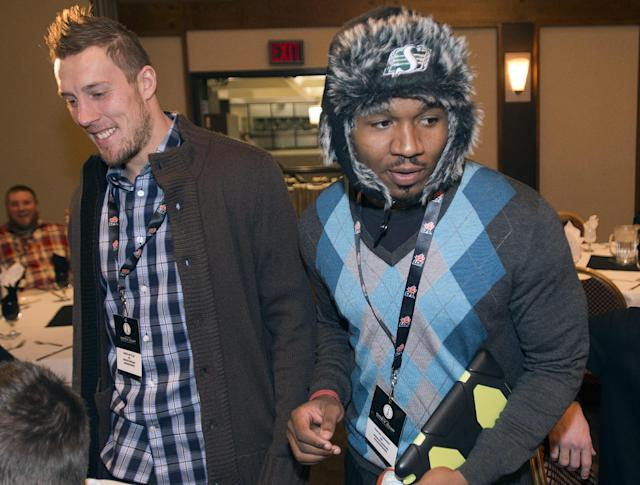 Saskatchewan Roughriders Carlos Thomas, right, is bundled up for the cold as he passes teammate Chris Getzlaf during a media luncheon Thursday, Nov. 21, 2013, in Regina, Saskatchewan. The Roughriders plays the Hamilton Tiger-Cats in the 101st Grey Cup on Sunday, for the Canadian Football League championship. (AP Photo/The Canadian Press, Ryan Remiorz)