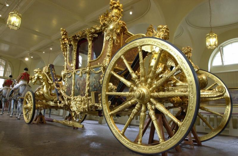 FILE - This June 15, 2001, file photo, shows the Queen's Gold State Coach in the Royal Mews in Buckingham Palace, in London, Fans of the British royals will want to include castles, Westminster Cathedral and other sites connected to Queen Elizabeth II and her family on any trip to England. (AP Photo/Richard Lewis, File)