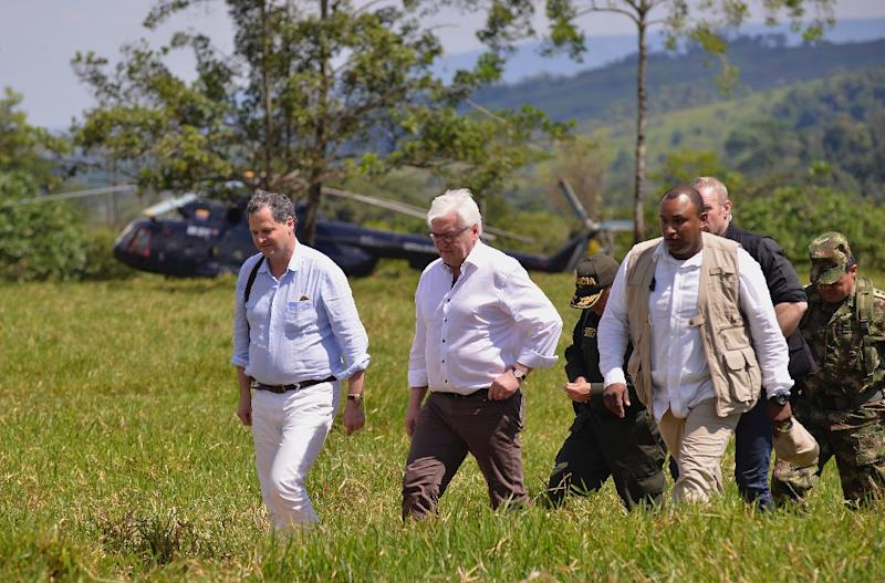 This handout picture shows Colombian High Commissioner for Peace Sergio Jaramillo (L) and German Foreign Minister Frank-Walter Steinmeier (2L) January 13, 2017 during a visit at one of the 26 UN-monitored camps that will receive FARC guerrillas (AFP Photo/OMAR NIETO)