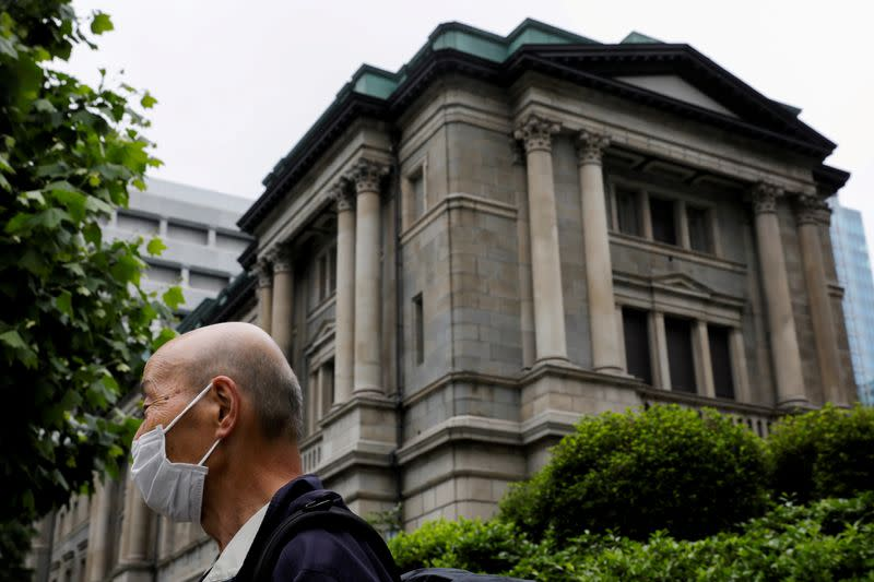 FILE PHOTO: A man wearing a protective mask stands in front of the headquarters of the Bank of Japan in Tokyo