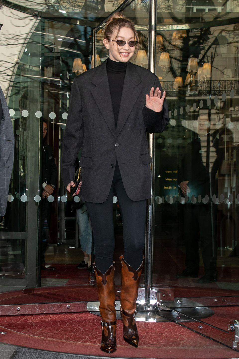 <p>In an oversized black blazer, black turtleneck, black jeans, angular sunglasses, and brown and black leather boots. </p>