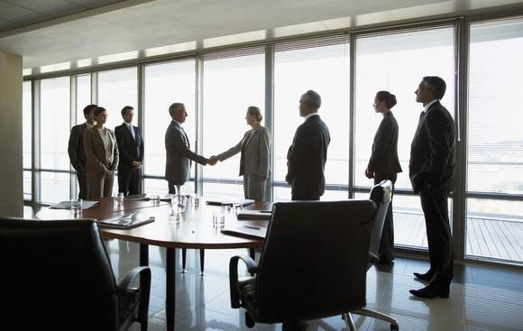 People in business attire shaking hands in a conference room.