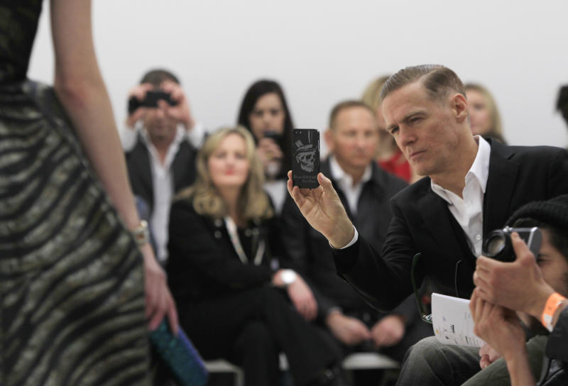 Bryan Adams takes a photograph of a model wearing a design created by Vivienne Westwood during London Fashion Week, at the Saatchi Gallery in West London, Sunday, Feb. 17, 2013. (Photo by Joel Ryan/Invision/AP)