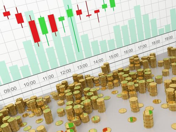 Stacks of gold coins in front of a candlestick chart with volume.